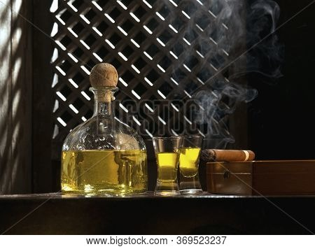 Close Up View Of Bottle Of Tequila Anejo And Cigar On Color Background