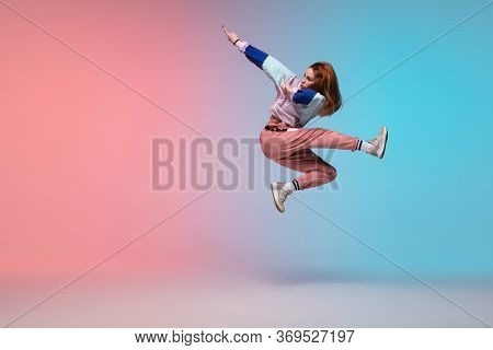 In Jump. Beautiful Girl Dancing Hip-hop In Stylish Clothes On Colorful Gradient Background At Dance