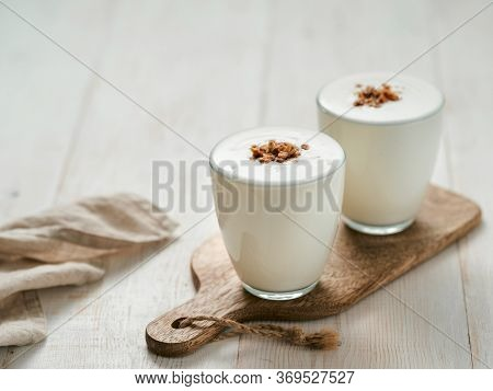 Kefir, Buttermilk Or Yogurt With Granola. Yogurt In Glass On White Wooden Background. Probiotic Cold