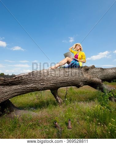 Woman with laptop on a tree