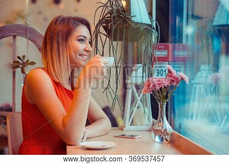 Enjoying Coffee. Beautiful Happy Smiling Young Woman With Cup Of Tea Looking Away Through The Window