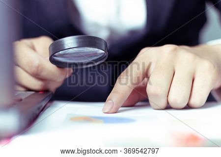 Businessmen Use A Magnifying Glass To Analyze The Company's Data And Statistics From The Chart.