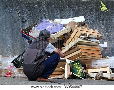 A Man Crouches In Front Of A Pile Of Garbage Against A Concrete Wall, Prospect Bolsheviks, Saint Pet