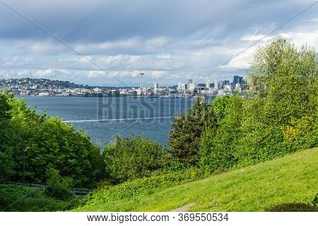 A View Of A Grassy Hill An The Seattle Skyline From West Seattle, Washington.