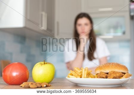 The Choice Between Unhealthy And Healthy Food. Burger And French Fries In Front Of An Apple, Tomato