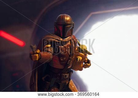 JUNE 1 2020: scene from Disney Plus Star Wars The Mandalorian - where the bounty hunter fires a blaster while holding The Child (aka Baby Yoda) -Hasbro action figure, red light reflection