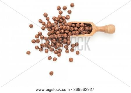 Chocolate corn balls in wooden scoop on white background