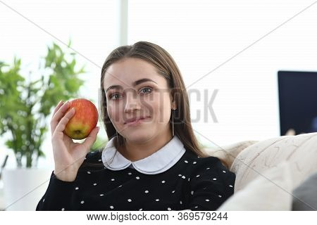 Girl Sitting At Home Couch With Apple In Her Hands. Girl Does Not Work, But Sits At Home. Comfortabl
