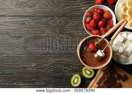 Composition With Ingredients For Chocolate Fondue On Wooden Background. Cooking Fondue