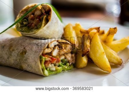 Tasty Wraps With Chicken, Avocado, Lettuce And French Fries On A Plate. Selective Focus