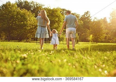 Happy Family Walking On The Grass In The Summer Park. Mother Father And Children Playing In Nature.