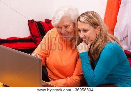 Young Blonde Woman Explains An Older An Laptop