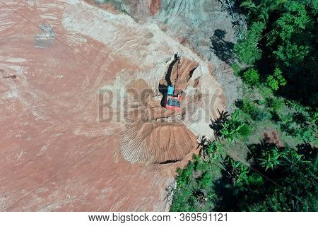 Deforestation. Excavator clearing land beside rainforest