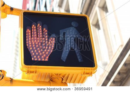 Halt signal with a red hand illuminated on the side of a traffic light at an intersection and pedestrian crossing poster