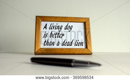 Wooden Picture Frame With Inscription 'a Living Dog Better Than A Died Lion' On Beautiful White Fon.