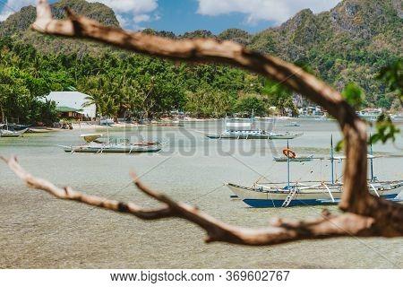 Fishing Boats Moored In Lagoon, Sandy Beach With Rocky Island Background Near El Nido On Palawan Isl