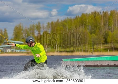 Fagersta, Sweden - Maj 26, 2020: Wakeboarder On Wakeboard Landed In Water Surrounded By Spray. Wakeb