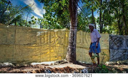 Kerala, India - March 11, 2014: A Fisherman Walking On A Street By The Backwaters Of Allepey Located