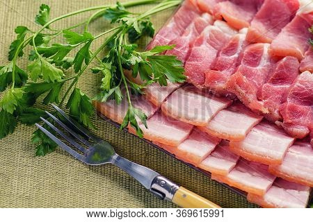 Sliced Bacon With Dill And Parsley. Still Life Of Bacon And Greens. Bacon Slices Close-up. On Natura