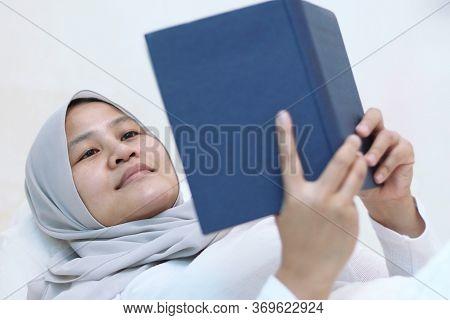 Asian Muslim Woman Reading Holy Quran On Bed, Reciting To Memorize Quran Before Sleep, Islamic Cultu
