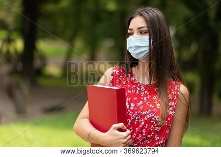 Masked woman student holding a book outdoor in a park