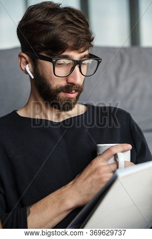 Image of focused man in wireless earphones drinking coffee and reading magazine while sitting in living room