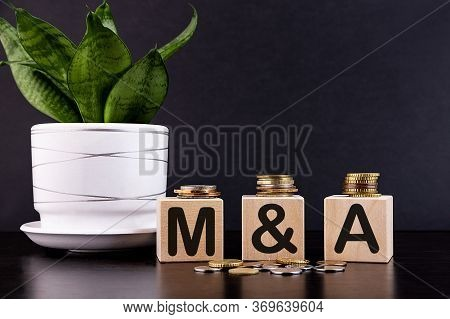 M And A Or Merger And Acquisition Text Written On A Wooden Cubes With Coins.