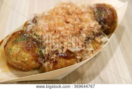 Closeup Japanese Takoyaki Octopus Balls Topped With Sauce And Shaving Dried Bonito In A Boat Shaped