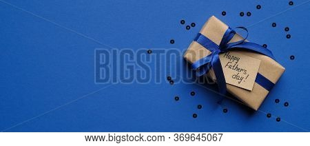 Happy Fathers Day Concept. Wide Banner Mockup With Gift Box Wrapped Craft Paper With Blue Ribbon And