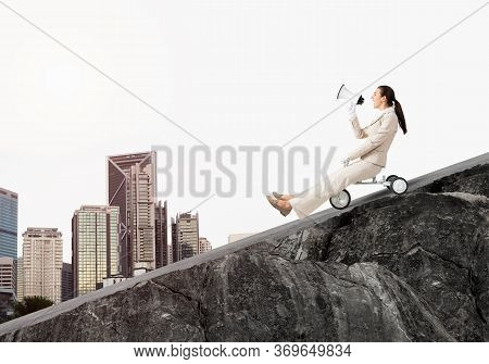 Woman Shouting Into Megaphone And Riding Downhill On Road. Young Employee In White Business Suit Goi