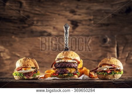 Double Beef Burger, Chicken Burger And A Beef Burger In A Rustic Wooden Environment With A Vintage K