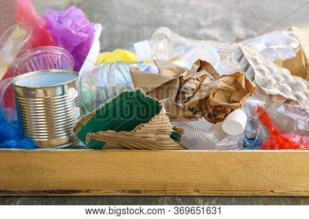 Box With Trash On Old Wooden Background.