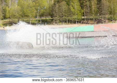 Wakeboarder On Wakeboard Landed In Water Surrounded By Spray. Wakeboarding Is An Extreme Sport.