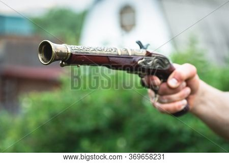 Old Musket Gun In A Pirate Hand Close Up. Duel.