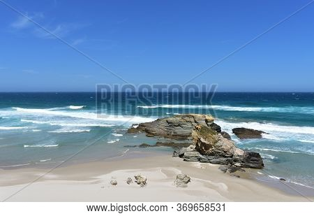 Summer landscape with wild beach with waves, rocks and blue sky. Viveiro, Spain.