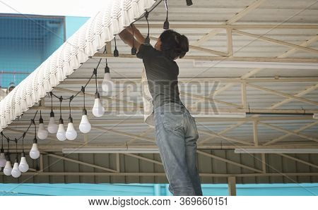 Bangkok, Thailand - June 04: Unnamed Man Hangs Light Bulbs On A Owning For Decoration In Bangkok On