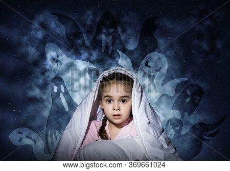 Scared Girl Hiding Under Blanket. Startled Kid Sitting In Bed On Night Sky Background. Little Girl A