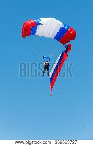 Military Skydiver With Russian Flag And Parachute In White, Blue And Red Colors On Blue Sky Backgrou
