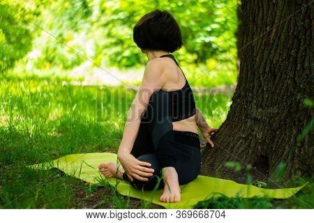A Short-cut Slender Brunette Woman Enjoys Exercising Hatha Yoga Barefoot Among The Grass Under Big T