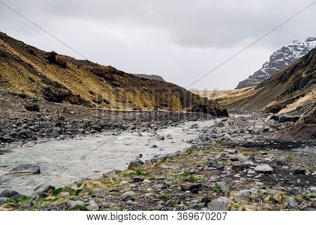 A Panoramic View Of The Valley In Iceland. The Shallow Mountain River Flows Through The Gorge Agains