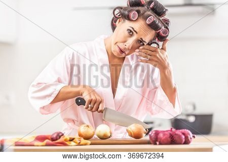 Woman In Hair Curlers And Nighgown Cries From Onion Cutting In The Kitchen, Wiping The Tear From Her