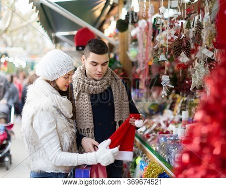 Handsome Man With Smiling Girlfriend At Counter Of X-mas Market. Shallow Focus.