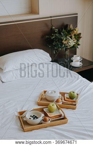 Breakfast In The Hotel. Porridge, Boiled Egg, Toast, Coffee, Porridge With Berries On A Tray