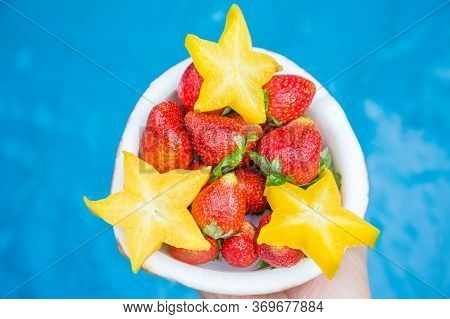Strawberries And Carambola Are Laid Out In A Half Of Coconut, On A Blue Background. Colorful, Summer