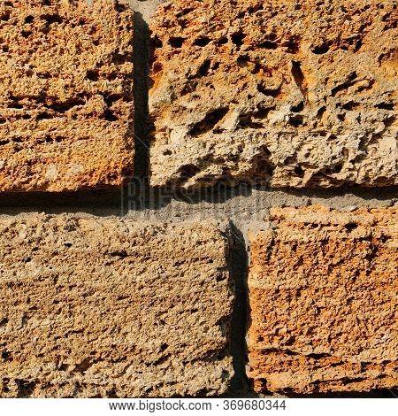 Brick Wall Of Yellow Shell Rock. Closeup Of Shellstone Texture. Background.