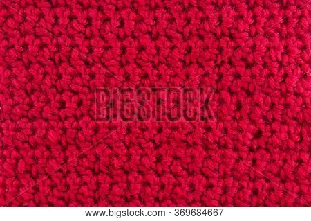 Woolen Vivid Red Knitted Background. Close Up. Background For Hobby. Woolen Thread. Knitted Stitches