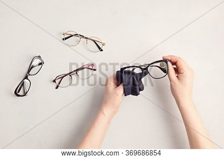 Woman Hand Cleaning Eyeglasses. Optical Store, Glasses Selection, Eye Test, Vision Examination At Op