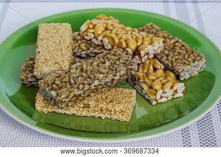 Kozinaki With Seeds, Nuts, Sesame Seeds And Honey In A Green Plate. Useful Snacks. Fitness Diet Food