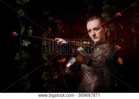 Valkyrie Girl In Shiny Military Armor And With A Spear In A Dark Room With Plants And Vines. Model D