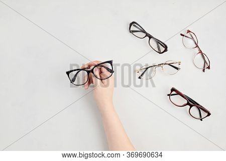 Woman Hand Holding Eyeglasses. Optical Store, Glasses Selection, Eye Test, Vision Examination At Opt